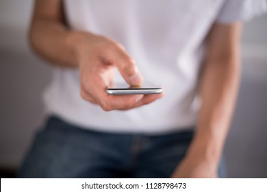 Young man using a touchscreen smartphone - Hands close-up - Using technology - Blue jeans and white t-shirt