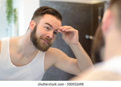 Young man using tweezers in the bathroom and looking in the mirror, personal hygiene and care concept