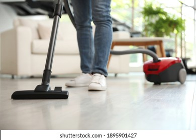 Young man using vacuum cleaner living room, closeup