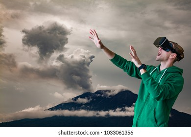 Young man using Virtual Reality glasses. Volcano background