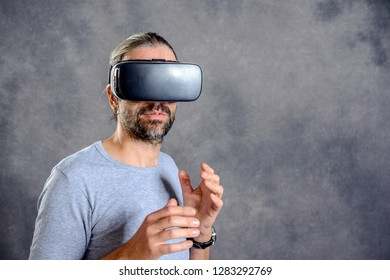young man using virtual reality glasses in front of gray background