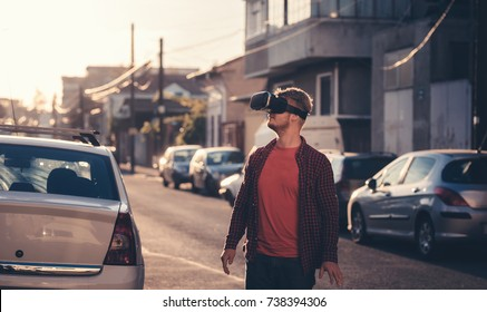 Young man using virtual reality technology glasses for entertainment VR device innovation headset with 360 3D vision experience game simulation. Best wearable gaming gadget goggles for cyberspace play