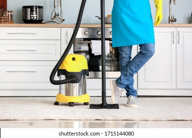 Young man with vacuum cleaner in kitchen