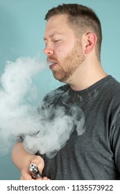 Young man vaping smoking an e-cigarette with a cloud of smoke obscuring his face as he holds the vaporizer in his hand