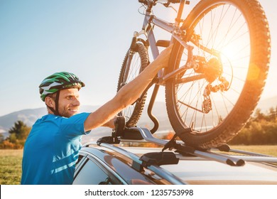 Young Man veared in cycling clothes and protective helmet instals his mountain bike on the car roof