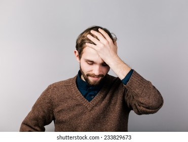 the young man is very upset with hand on head