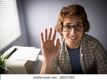 Young man video calling and waving hand with funny expression.