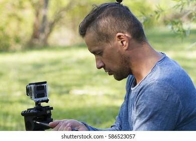 young man with a video camera filming outdoors in summer