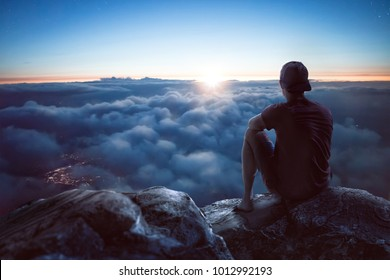 Young man with view over the clouds