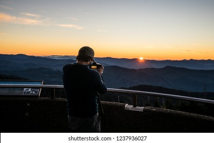 Young man viewing sunrise at the top of Clingman's Dome, a very popular tourist destination in The Great Smoky Mountains/USA.