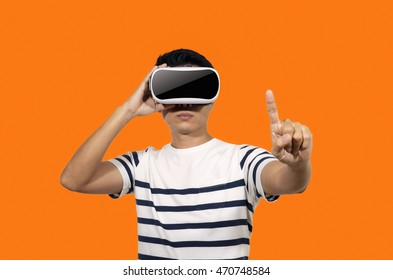 Young man with a virtual reality headset stand on orange background indoor.