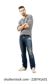 Young man in v-neck t-shirt and ripped jeans looking away with crossed arms. Full body length isolated over white background.
