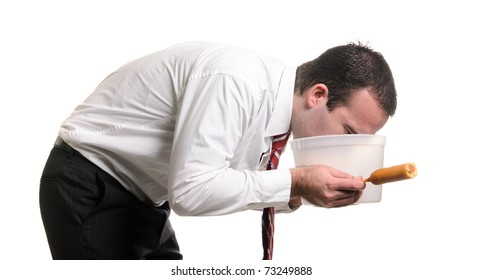 A young man is vomiting into a pail after eating a bad corn dog and getting food poisoning, isolated against a white background.