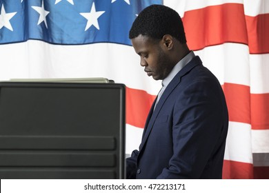 A young man in a voting booth, side view