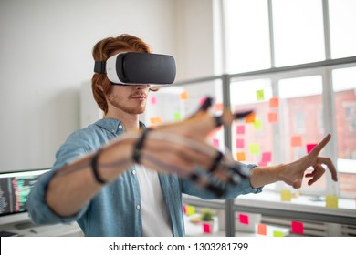 Young man with vr goggle and sensors on fingers making virtual presentation while working in office
