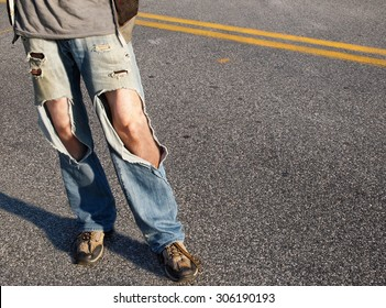 A young man, from the waist down,  in a causal t-shirt and ripped jeans with hair legs exposed stands in the road.
