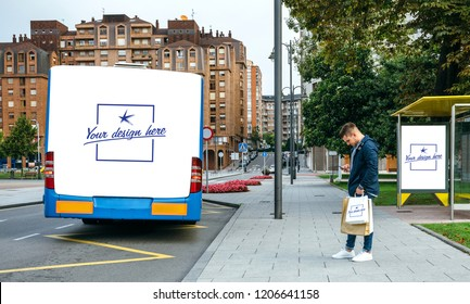 Young man waiting for the bus while looking at the mobile. Customizable rear end of bus, shopping bag and bus canopy
