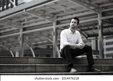 Young man waiting and sitting alone on the stair case outdoor. Handsome man sitting outside concerned on the stairs waiting for someone or something.man in white shirt sitting alone on stairs outside.