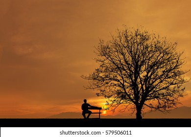 Young man waiting someone, man sitting on the bench under a tree.
