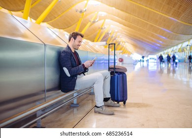 young man waiting and using mobile phone at the airport