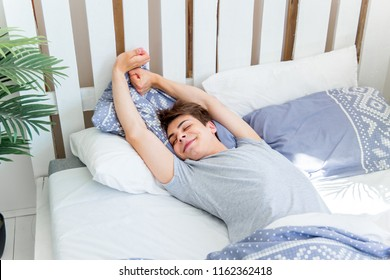 A young man waking up in bed in the morning