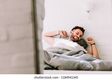 Young man waking up in the bed in the morning
