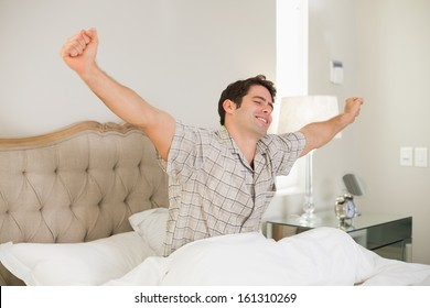 Young man waking up in bed and stretching his arms at home