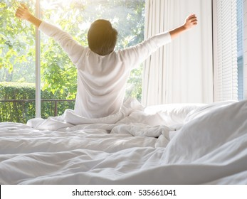 Young man waking up and rise hands stretching on white bed in the morning with sunlight through window