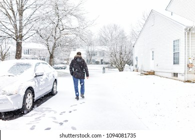 Young man walking by car in driveway in neighborhood with snow covered ground during blizzard white storm, snowflakes falling in Virginia suburbs, single family homes to check mail in mailbox