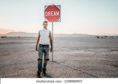 Young man walking by the dream sign in the middle of a desert at the Burning man - art and music festival. Sign to keep dreaming.