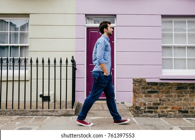 Young man walking, casual and happy on an autumn day in the street of London. Lifestyle Photography