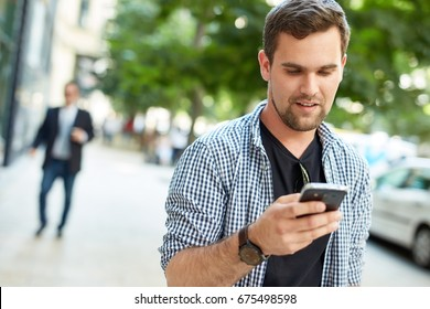 Young man walking in the city, using mobilephone.