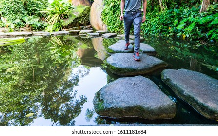Young man walking crossing a river on stones.