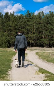 young man walking with dog in forest