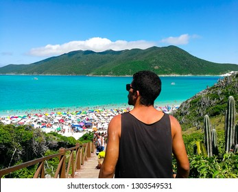 Young man walking down the famous steps of the stair in Pontal do Atalaia beach, in Brazil. One of the most beautiful beaches in Arraial do Cabo, Rio de Janeiro.