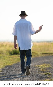 Young man walking in the field and is frustrated