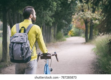 Young Man Walking With His Bike
