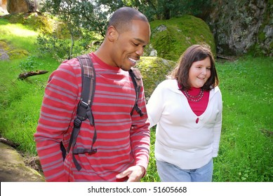 Young man walking with his visually impaired friend through a forest