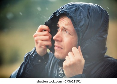 Young man walking in nature during heavy rain.