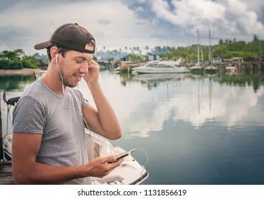 Young man walking near beautiful bay using phone and headphones for communicate with friends and listening music