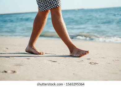 Young man walking on the beach.