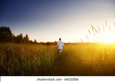young man walking on field