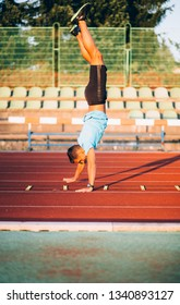 Young man walking on hands on running track