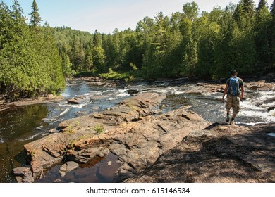 young man walking on the side of a river in La Mauricie National Park