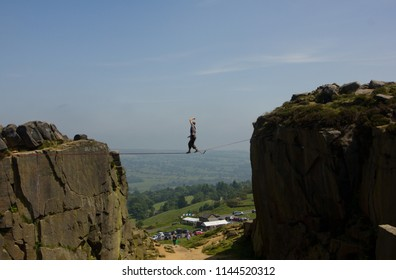 Young man walking on slackline / tight rope with beautiful landscape and blue sky in the background high above the ground.