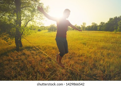 Young man walking on slackline in the meadow at sunset.