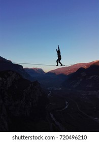 Young man walking on slackline above the mountains