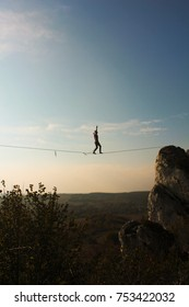 Young man walking on slackline /  tight rope with sky and beautiful landscape in the background. Jura, Poland