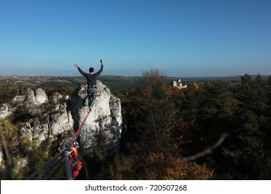 Young man walking on slackline/tight rope above the rocks and castle.