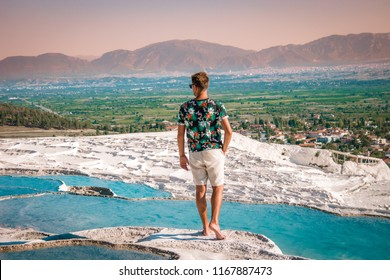 young man walking at the pool in natural bath , Natural travertine pools and terraces in Pamukkale. Cotton castle in southwestern Turkey Pamukkale